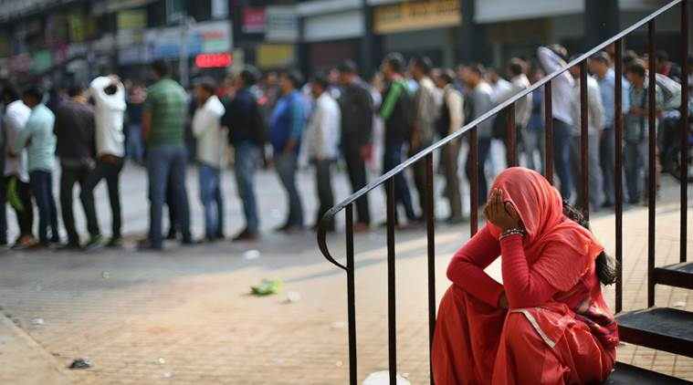 A woman takes rest next to a queue outside an ATM in Nehru Place on Sunday. Express photo by Oinam Anand. 04 December 2016